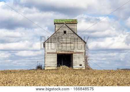 A rustic old barn stands dramatically against a cloudy blue sky in a rural Midwestern cornfield.