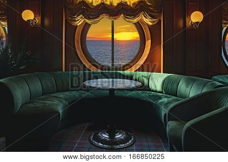 Lounge on a cruise ship with tables and armchair in the sunset at sea
