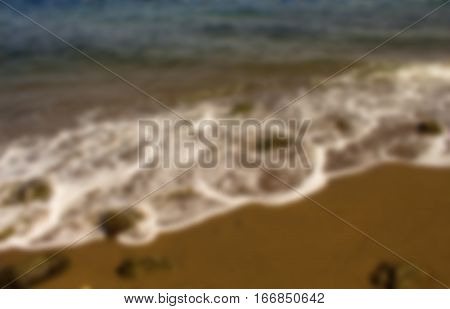 Beach with sea wave blurry photo for background. Warm tropical beach blurry image. Seaside bokeh image. Abstract exotic island travel blurry landscape. Sea wave with white foam blurry picture.