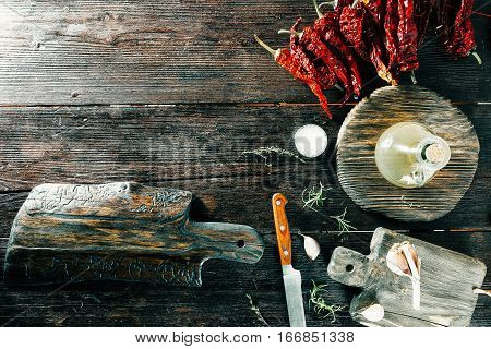 Vinegar, chili, spices and condiments on wooden cutting boards