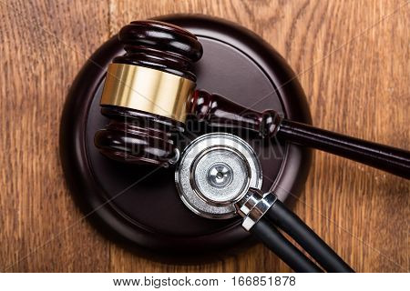 High Angle View Of Brown Gavel With Medical Stethoscope At Wooden Desk In Courtroom
