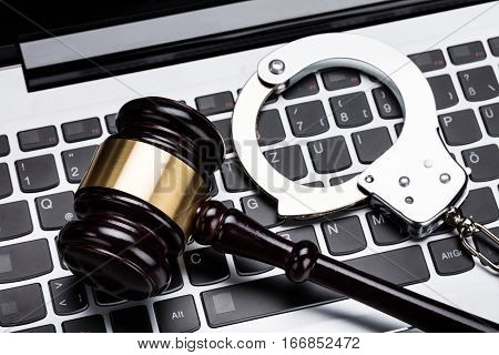 High Angle View Of Judge Gavel And Handcuff On Laptop Keyboard
