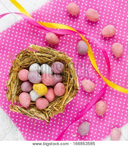 Traditional Easter treats for kids - Easter chocolate candy eggs in nest on pink napkin top view