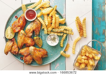 Grilled chicken wings with potato fries and dipping sauces. Top view, copy space