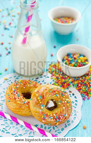 Donuts with colorful sprinkles and milk on blue background