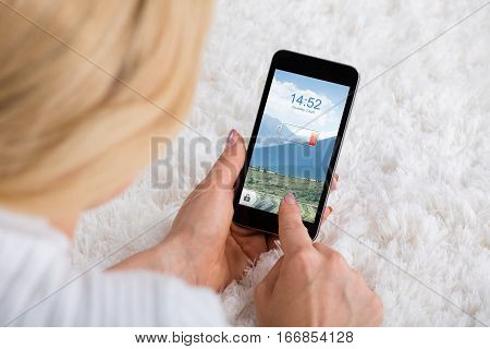 Close-up Of Woman Hand Holding Mobile Phone With Low Battery On Carpet