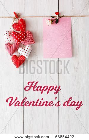 Happy valentine background with red pillow sewed heart on clothespins and paper card with rose flower on rustic wood planks. Happy lovers day mockup, copy space