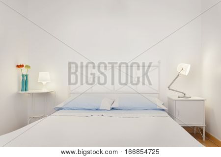 Brightly lit and Fresh Bedroom Suite with blue pillows