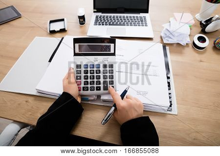 Close-up Of A Accountant Calculating Invoice Using Calculator On Office Desk