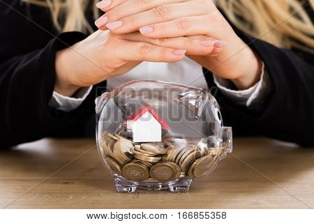 Close-up Of A Businesswoman Protecting Her Savings With House Model In A Piggybank. Real Estate Investment Concept