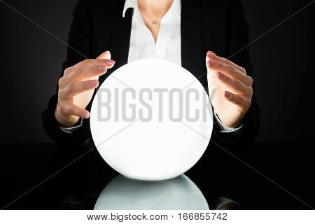 Businesswoman Hands On Crystal Ball On Black Background. Fortune Teller Predicting Future
