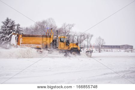 Heavy industrial dump truck with attached plow speeding down a highway clearing snow off the road in rural landscape