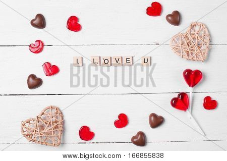 Chocolate candies and red lollipops. The form of hearts. The words