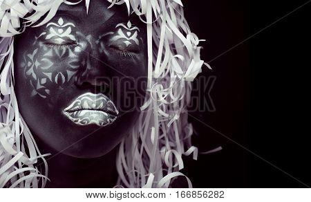 creative make up like Ethiopian mask, white pattern on black face close up, halloween horror