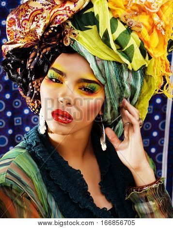 beauty bright woman with creative make up, many shawls on head. ethno look