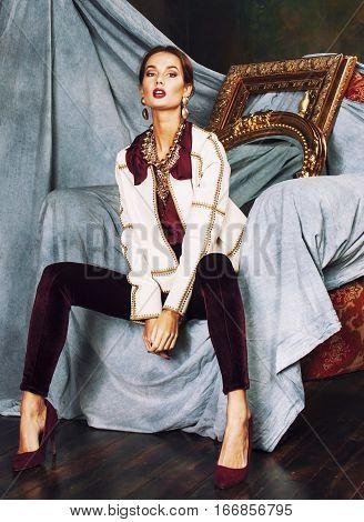 beauty rich brunette woman in luxury interior near empty frames, vintage elegance, gold
