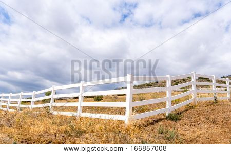 Sunlit white fence forming leading horizontal lines.