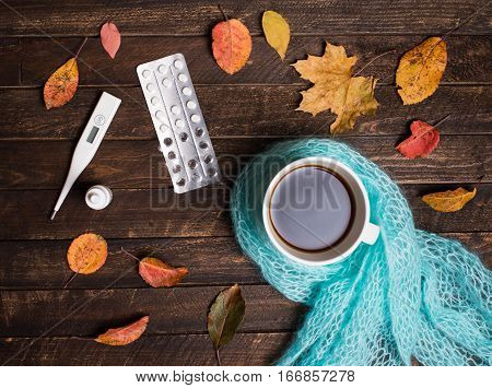 Hot herbal tea pills nasal drops thermometer and autumn leaves on rustic dark wooden background. Top view. Fall and health care. Herbal medicine.