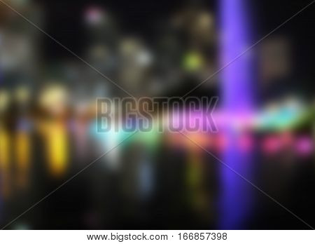 Colorful fountains by night blurry image. Nightlife of big city bokeh. Colored lights and water reflections in park defocused image. City night blurry illustration. Big city lights in darkness blur