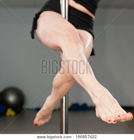 Pole fitness class legs in focus, toned image, square image