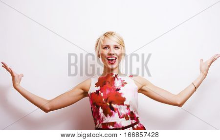 young pretty blonde girl presenting something at white copy space, isolated