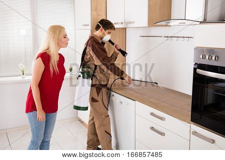 Exterminator Worker Spraying Pest Control Pesticide In Front Of Young Woman Standing In Kitchen