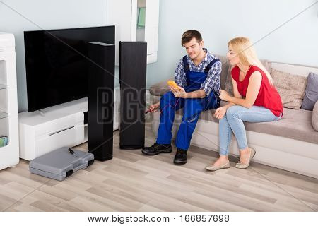 Technician Checking TV Speaker Sound System With Multimeter In Front Of Woman At Home
