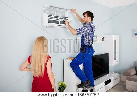 Woman Looking At Young Male Technician Servicing Or Repairing Air Conditioner At Home