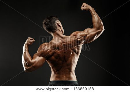 Back view of Unrecognizable man, strong muscles posing with arms up