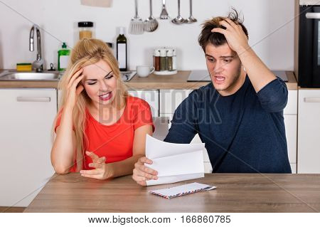 Young Worried Couple Reading Letter And Bill In The Kitchen At Home. Bad News Concept