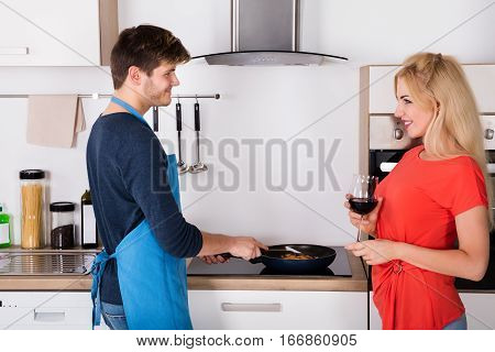 Husband And Wife Having Good Conversation While Preparing Dinner In Kitchen