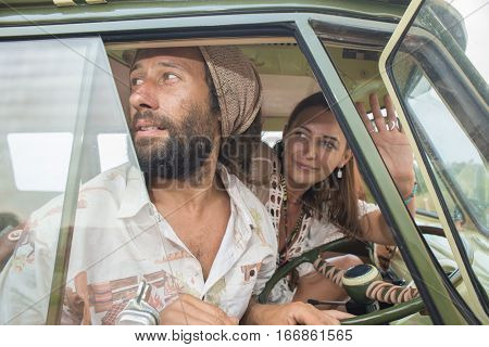 A young couple looks and waves as they set of on a road trip in their old retro combi van.