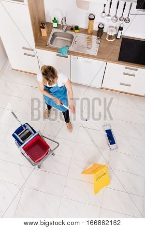 High Angle View Of Young Housemaid Mopping Floor In Kitchen