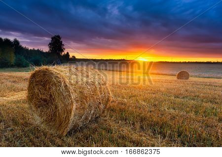 Sunset Over Beautiful Field With Straw Bales.