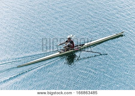 Single scull sport rowing on lake , toned image