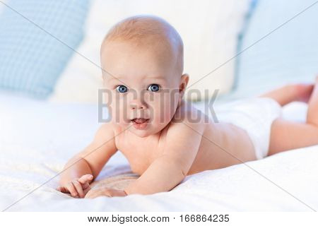 Baby boy wearing diaper in white sunny bedroom. Newborn child relaxing in bed. Nursery for children. Textile and bedding for kids. Family morning at home. New born kid during tummy time with toy bear.