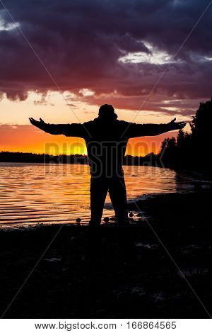 Silhouette of Man Raising His Hands or Open arms when sun rising up.