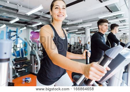 Young fit woman using an elliptic trainer in a fitness center and smiling