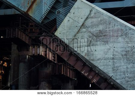 Bridge under construction with massive industrial structures