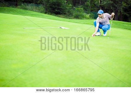 Golf Player Marking Ball On The Putting Green