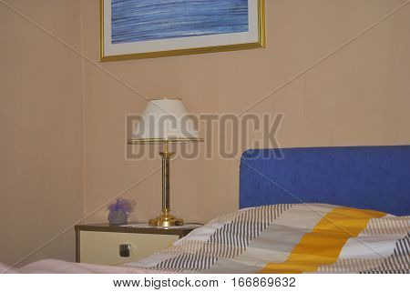 Part of bedroom with part of bed, nightstand and lamp.