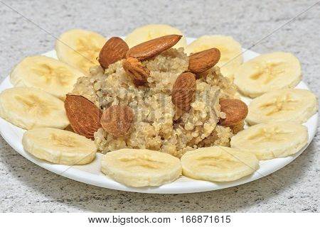 Quinoa served with banana, almonds and honey. Fresh morning breakfast