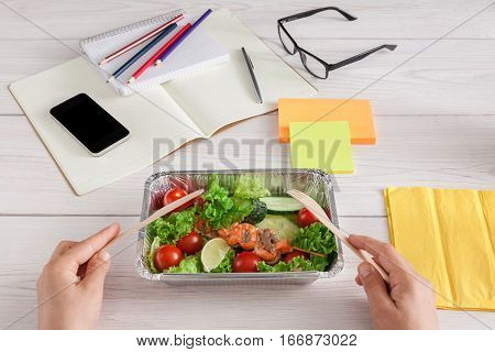 Healthy business lunch in the office, pov view of eating person. Salad plate with salmon on white wooden desk near mobile phone and open organizer. Snack at break time