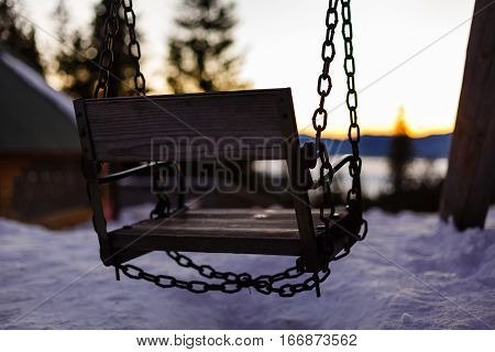 Abstract winter scene with a garden swing covered with snow, appearing to invite everyone to take a break, have a snack and enjoy the landscape and generally the unique moments of the life.