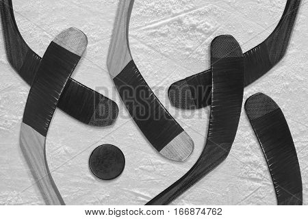 Hockey puck and sticks on black ice hockey rink