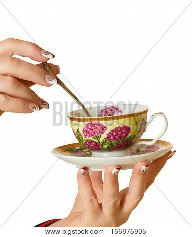 female hands with manicure hold a cup with a saucer