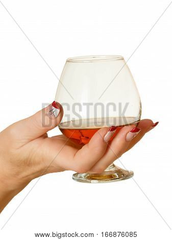 female hand with manicure holds a glass of brandy