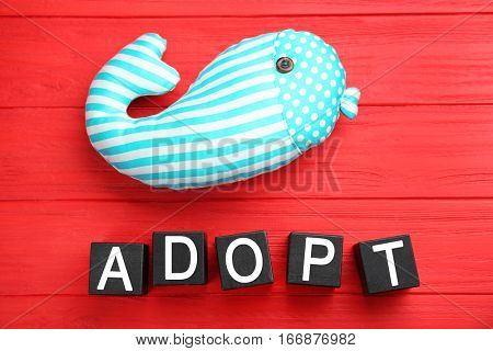 Black cubes with word ADOPT and whale toy on color wooden background