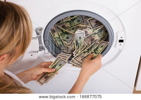 Close-up Of Person Hand Inserting Dirty Money In Washing Machine