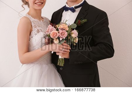 Closeup of newlyweds holding wedding bouquet on white background